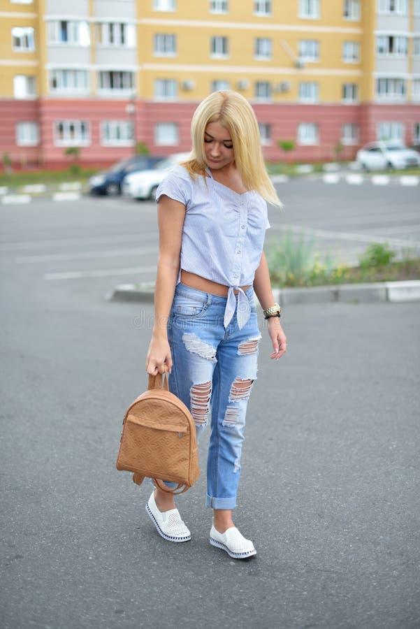 Una chica joven camina abajo de la calle con una mochila beige en tejanos rasgados Tejanos rasgados de moda en las piernas de una fotografía de archivo libre de regalías
