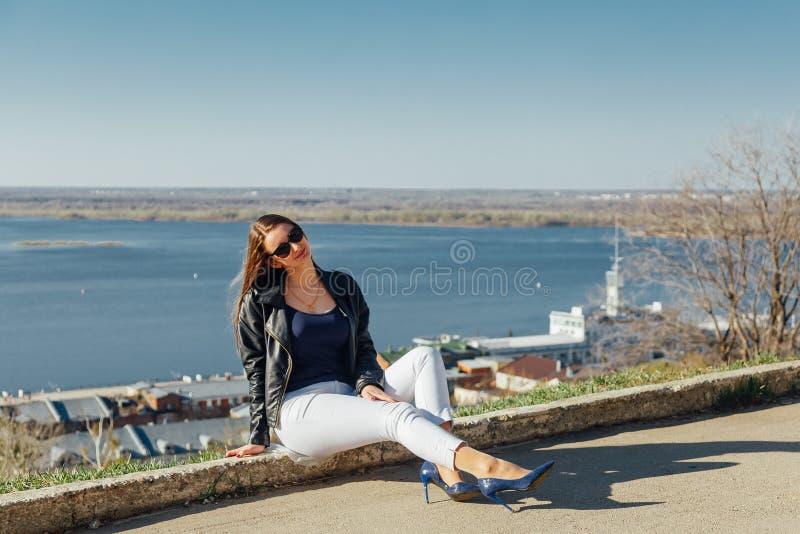 Una chica joven camina en el terraplén de la bahía de la ciudad imagen de archivo