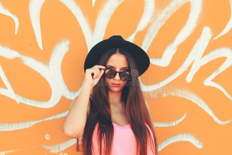Una chica joven colorida que mira la cámara que lleva un sombrero negro y gafas de sol de moda foto de archivo