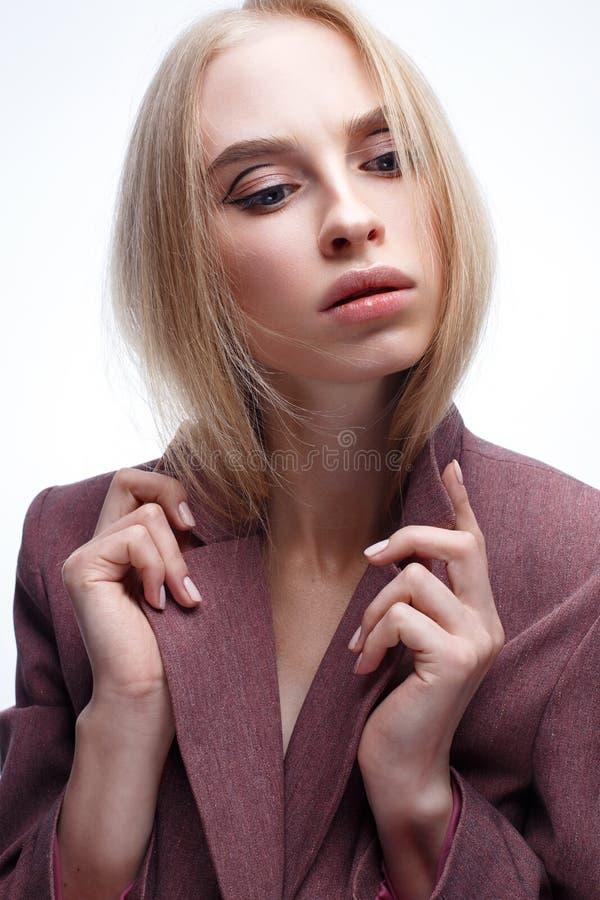Una chica joven con maquillaje largo del pelo recto y del desnudo Modelo hermoso en una capa rosada Blonde en una chaqueta Bellez foto de archivo libre de regalías