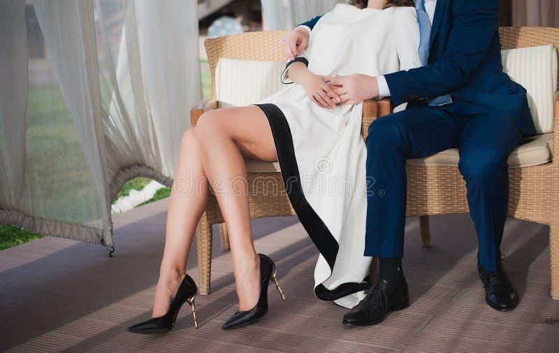 Una chica joven con sentarse y abrazos largos de las piernas el hombre foto de archivo