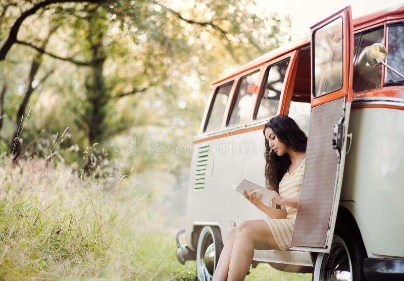 Una chica joven con un libro por un coche en un roadtrip a través del campo, lectura imagen de archivo libre de regalías