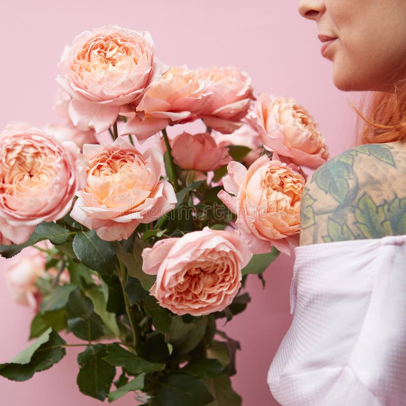 Una chica joven con un tatuaje est? sosteniendo un ramo de rosas rosadas elegantes alrededor de su fondo rosado imágenes de archivo libres de regalías