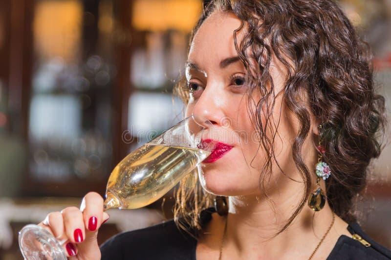 Una chica joven con un vidrio de vino en un ajuste hermoso imagen de archivo libre de regalías