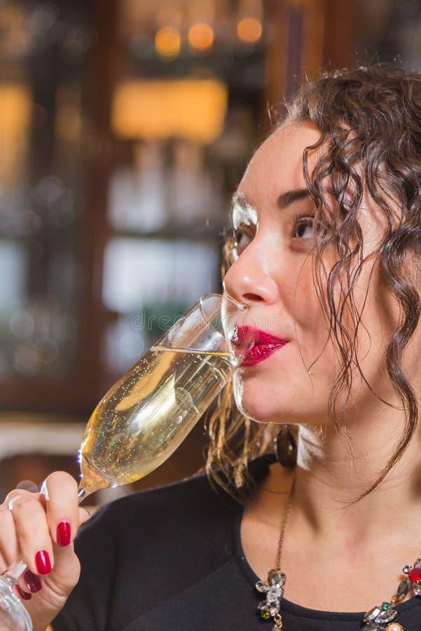 Una chica joven con un vidrio de vino en un ajuste hermoso fotos de archivo