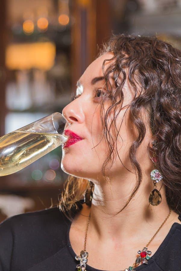 Una chica joven con un vidrio de vino en un ajuste hermoso fotos de archivo libres de regalías