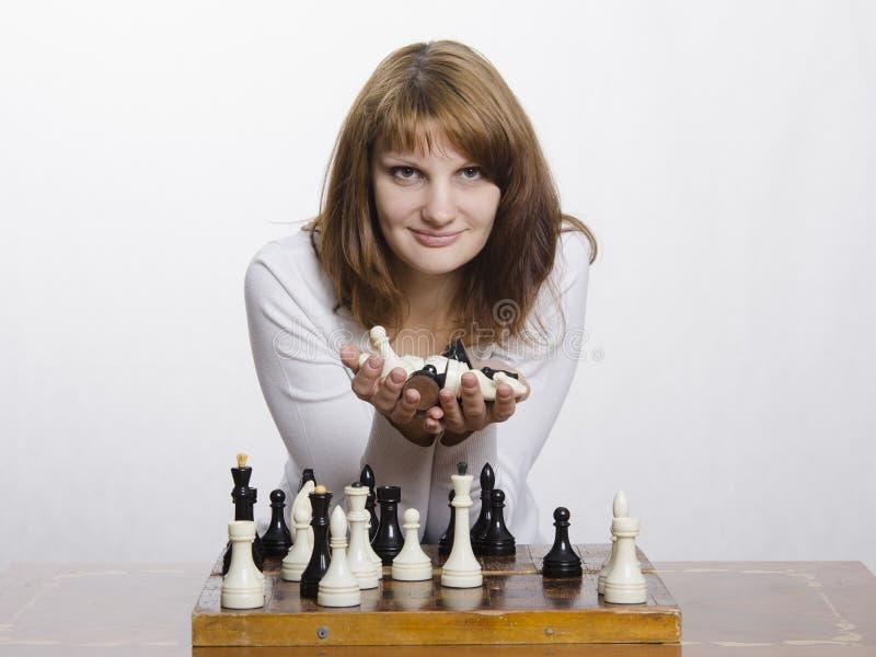 Una chica joven con una figura de un caballo, en el tablero de ajedrez fotografía de archivo