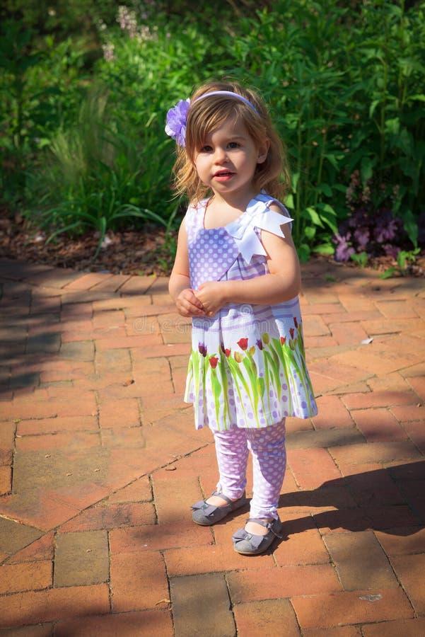 Una chica joven de 3 años camina en un jardín botánico imágenes de archivo libres de regalías