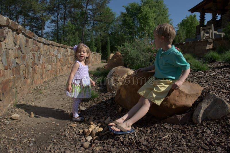 Una chica joven de 3 años y un muchacho de 5 años descansan en un jardín de piedras imagen de archivo libre de regalías