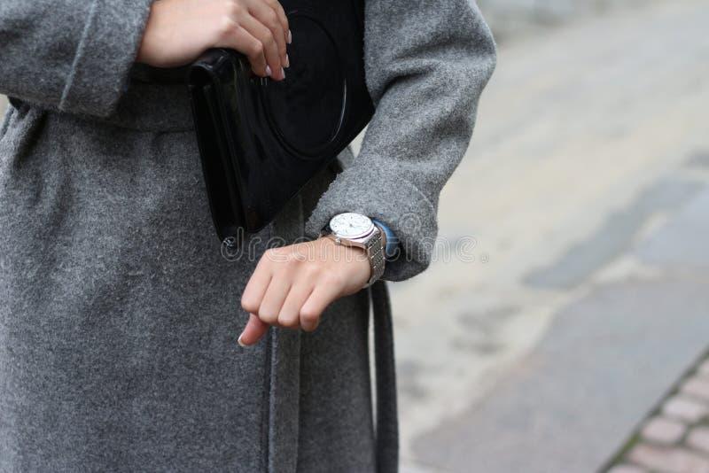 una chica joven en una capa gris mira su reloj, comprueba el tiempo, mira su reloj la prisa a una reunión, sea atrasada puntualid fotografía de archivo libre de regalías