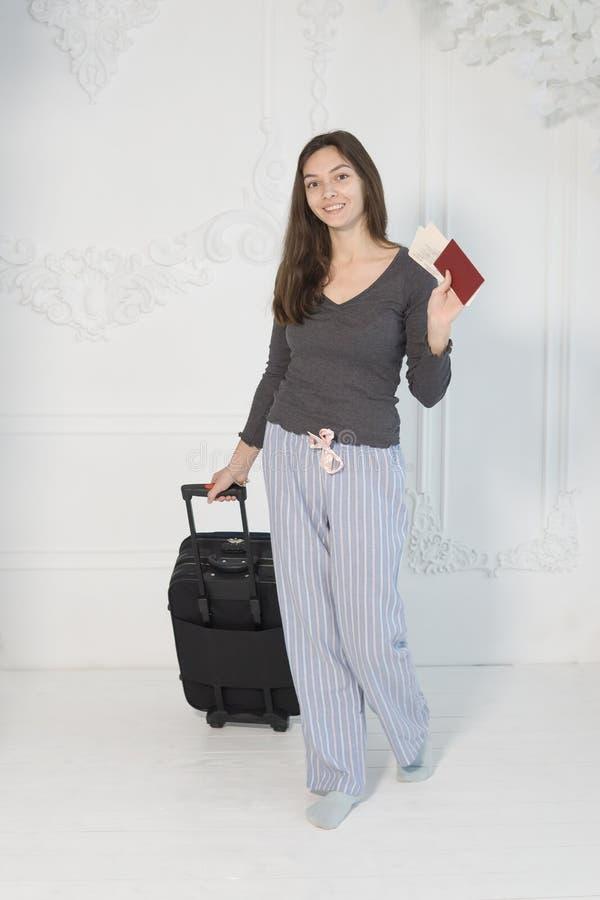 Una chica joven en una chaqueta marrón con los boletos y un pasaporte en sus manos mira la cámara, sonríe, lleva una maleta fotos de archivo libres de regalías