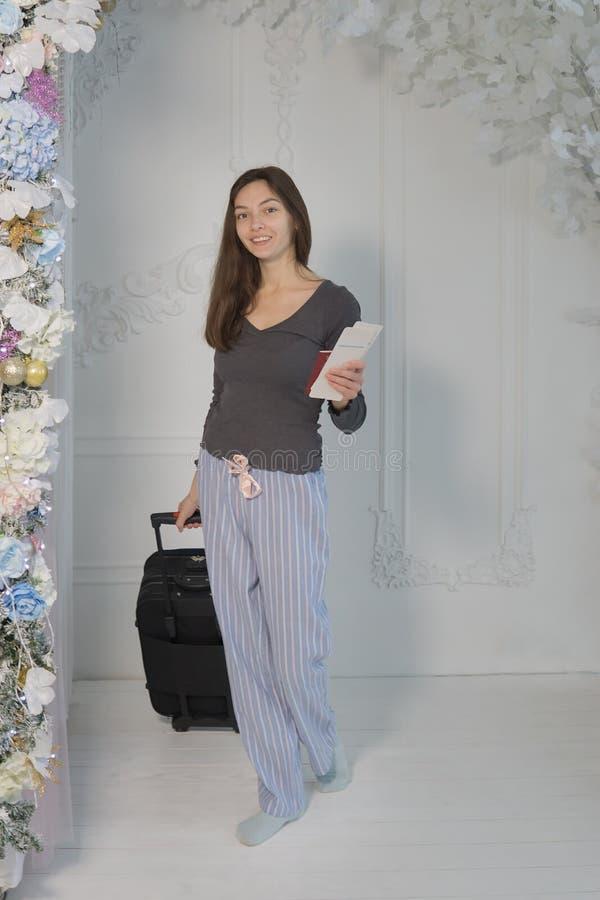 Una chica joven en una chaqueta marrón con los boletos y un pasaporte en sus manos mira la cámara, sonríe, lleva una maleta foto de archivo libre de regalías