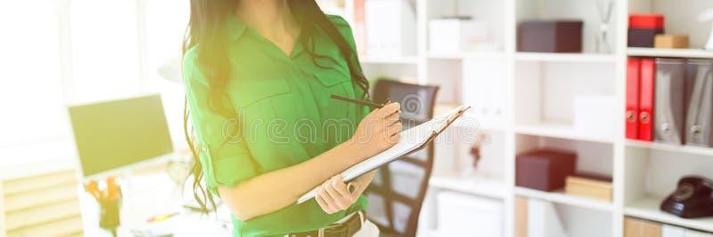 Una chica joven en la oficina está sosteniendo un lápiz y una hoja para las notas fotos de archivo libres de regalías