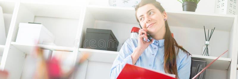 Una chica joven en la oficina se está colocando cerca del refugio, está hablando en el teléfono y está enrollando a través de la  imagenes de archivo