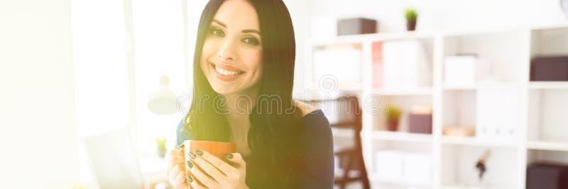 Una chica joven en la oficina sentada abajo en la tabla y sostenía una taza roja en sus manos fotos de archivo libres de regalías
