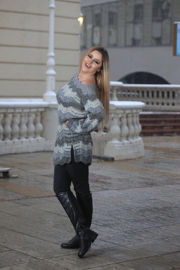 Una chica joven en una posición derecha, vestida en un gris foto de archivo libre de regalías