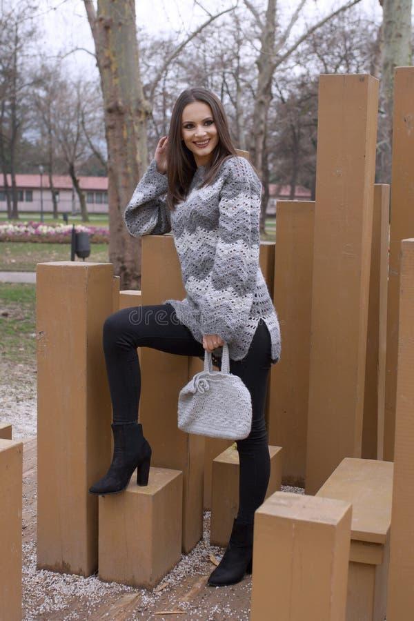 Una chica joven en una posición derecha, vestida en un suéter gris fotografía de archivo libre de regalías
