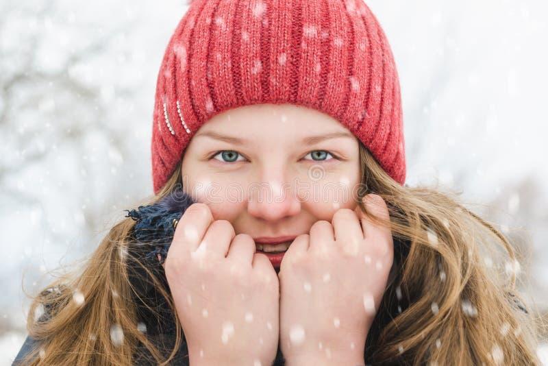 Una chica joven en un sombrero coral-coloreado está sosteniendo un cuello en sus manos para hacerlo más caliente, y está sonriend fotos de archivo libres de regalías