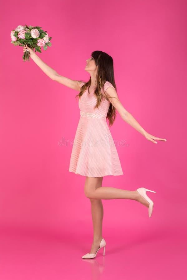 Una chica joven en un vestido festivo está cogiendo un ramo de flores en rosa foto de archivo libre de regalías