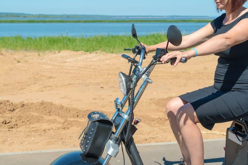 Una chica joven en un vestido negro con el pelo rojo que conduce su motocicleta eléctrica de tres ruedas a lo largo de la playa e imagen de archivo