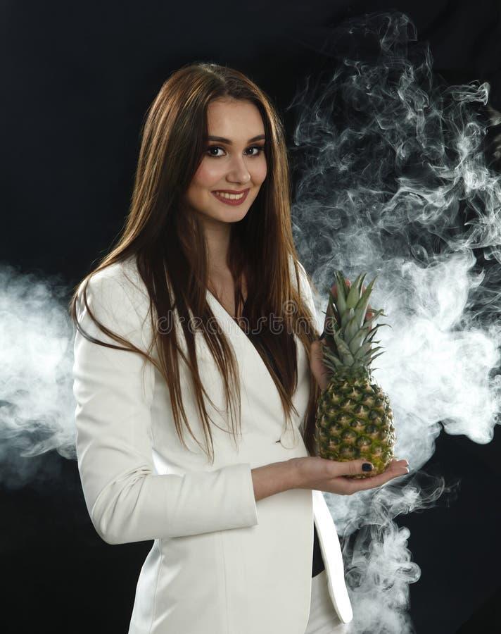 Una chica joven en una chaqueta del blanco sostiene una piña en sus manos y sonrisas en un fondo negro, cubierto con el vapor del imagenes de archivo