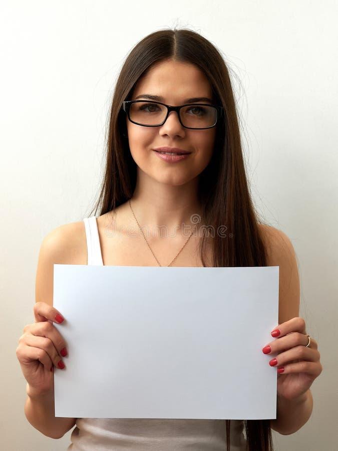 Una chica joven en vidrios muestra una hoja en blanco Retrato colorido en un fondo blanco Espacio para el texto La morenita está  fotos de archivo