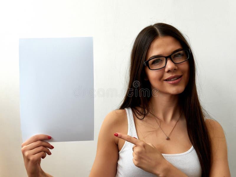 Una chica joven en vidrios muestra una hoja en blanco Retrato colorido en un fondo blanco Espacio para el texto La morenita está  foto de archivo