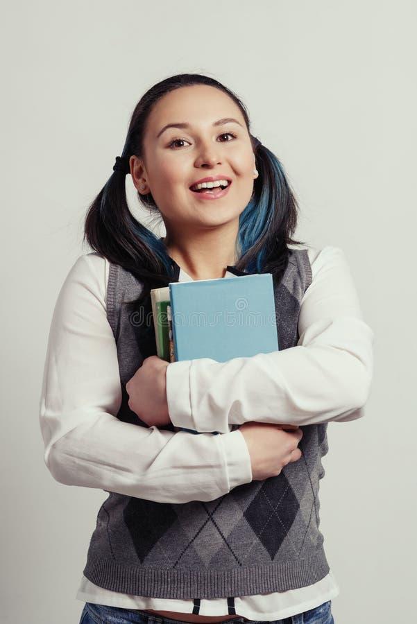 Una chica joven es un estudiante de un estudiante de la escuela secundaria con una pila de libros de texto en sus manos En el fon imagen de archivo