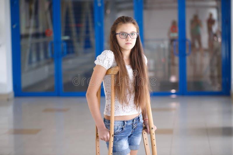 Una chica joven está en las muletas en el pasillo del hospital foto de archivo