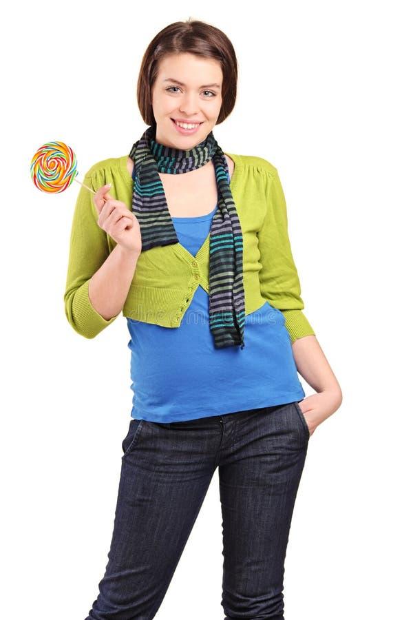 Una chica joven feliz que sostiene un lollipop fotografía de archivo
