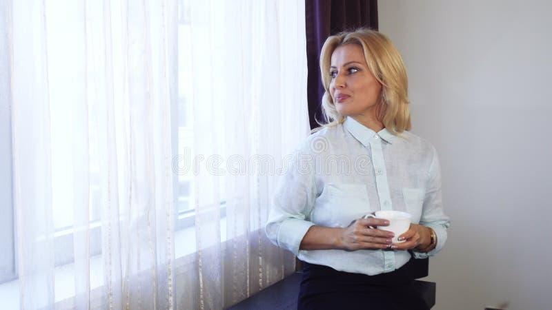 Una chica joven hace una pausa la ventana y mira hacia fuera la ventana foto de archivo libre de regalías