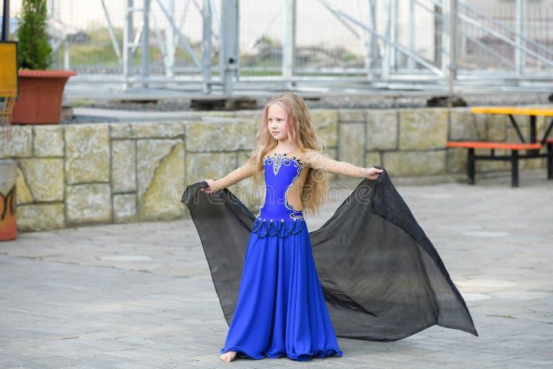 Una chica joven hermosa cabe a un bailarín moderno en un traje azul, bailarín joven, bailando y saltando, danza con una bufanda C imágenes de archivo libres de regalías