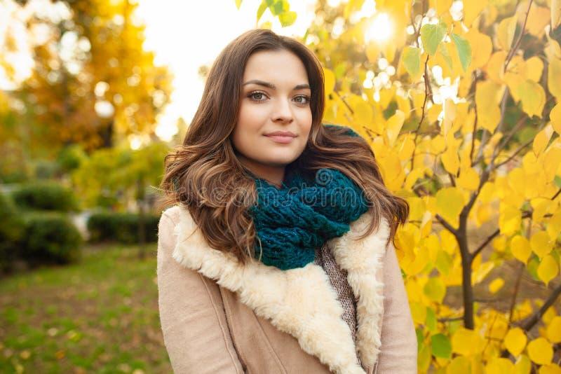 Una chica joven hermosa camina a través del parque del otoño en el fondo de hojas brillantemente coloreadas fotografía de archivo libre de regalías