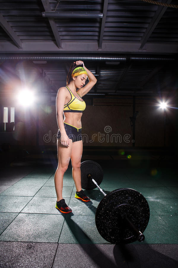 Una chica joven hermosa en el gimnasio entrena a los músculos de las piernas y la parte posterior, deadlift de los ejercicios del imágenes de archivo libres de regalías