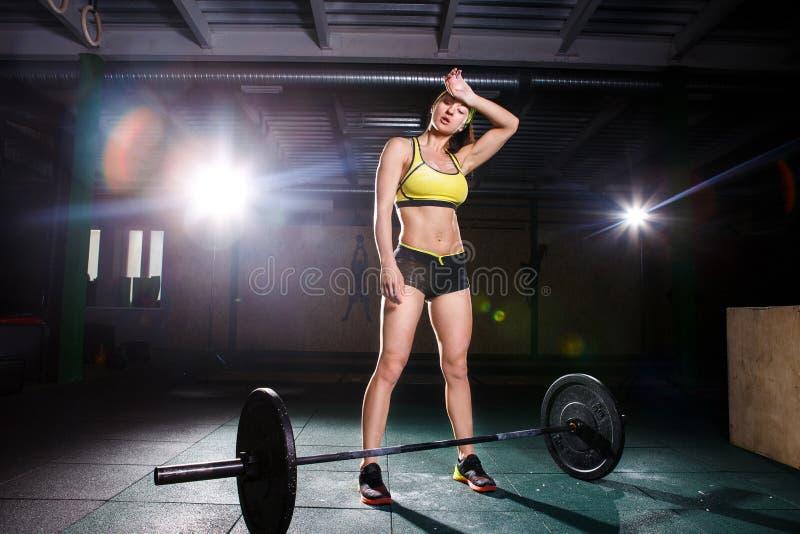 Una chica joven hermosa en el gimnasio entrena a los músculos de las piernas y la parte posterior, deadlift de los ejercicios del imagen de archivo