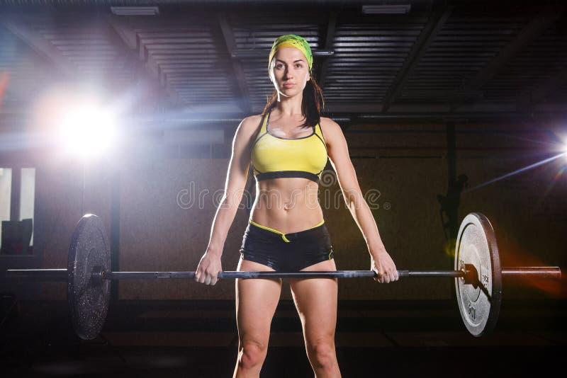 Una chica joven hermosa en el gimnasio entrena a los músculos de las piernas y la parte posterior, deadlift de los ejercicios del fotografía de archivo