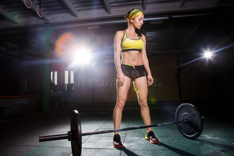 Una chica joven hermosa en el gimnasio entrena a los músculos de las piernas y la parte posterior, deadlift de los ejercicios del foto de archivo libre de regalías