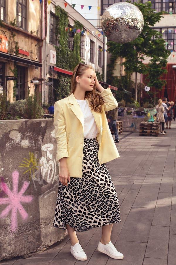 Una chica joven hermosa rubia en una chaqueta amarilla se coloca contra la perspectiva de la ciudad de Tbilisi georgia foto de archivo libre de regalías