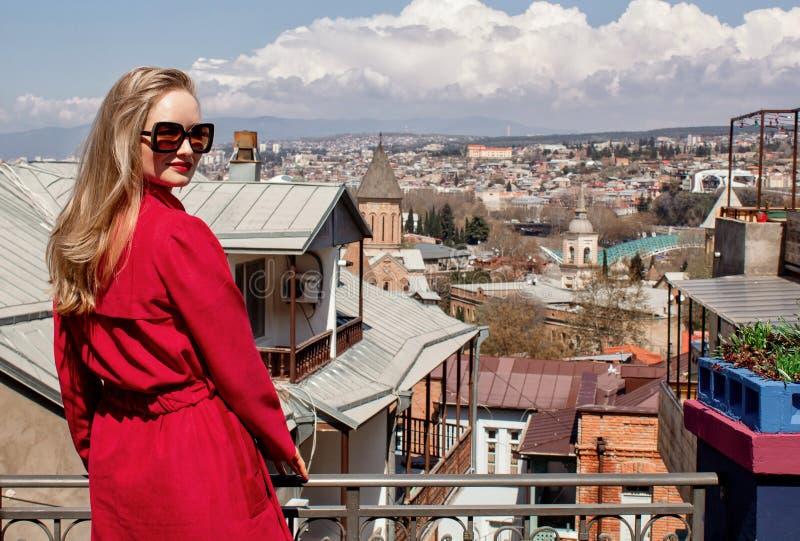Una chica joven hermosa rubia en las gafas de sol y una capa roja, soportes en el fondo de la ciudad de Tbilisi fotografía de archivo