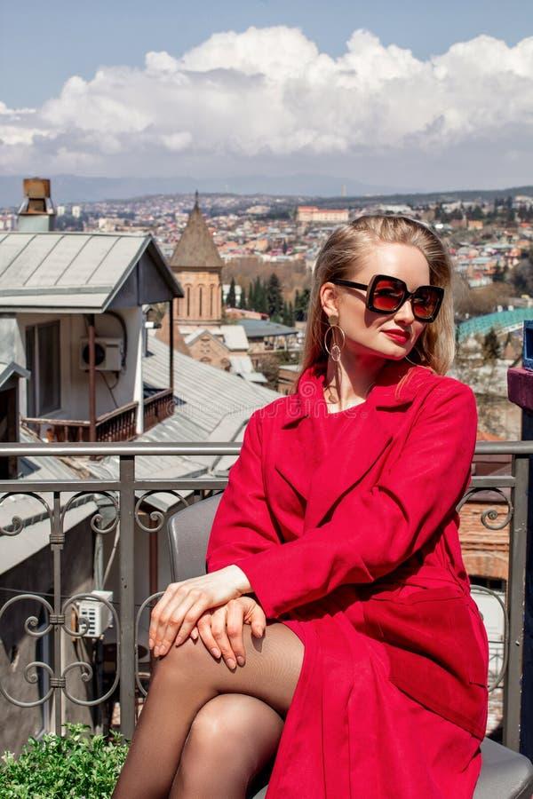 Una chica joven hermosa rubia en las gafas de sol y una capa roja, soportes en el fondo de la ciudad de Tbilisi imagenes de archivo
