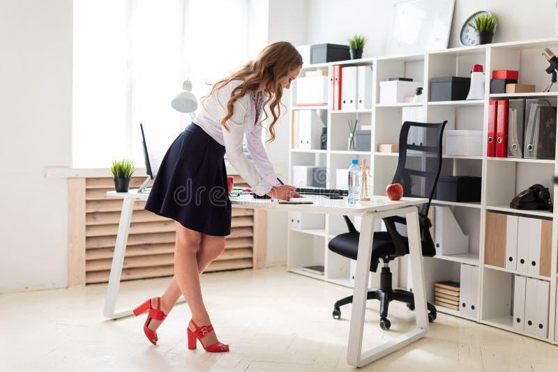Una chica joven hermosa se coloca cerca de una tabla en la oficina y escribe en un cuaderno fotografía de archivo libre de regalías
