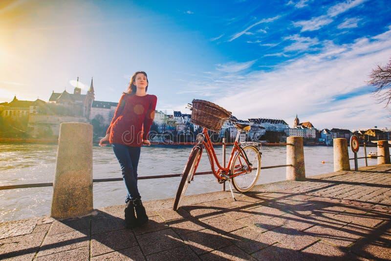 Una chica joven hermosa se coloca en el terraplén cerca de una bicicleta de la ciudad con una cesta de rojo en Suiza, la ciudad d fotos de archivo