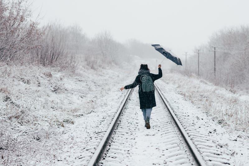 Una chica joven linda sostiene el paraguas en las manos de la estación del invierno imagenes de archivo