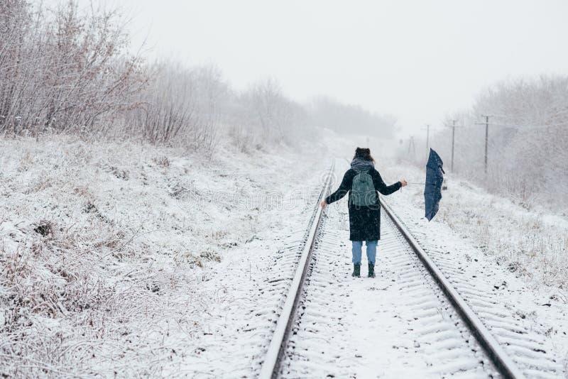 Una chica joven linda sostiene el paraguas en las manos de la estación del invierno fotos de archivo libres de regalías