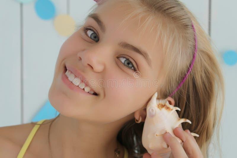 Una chica joven lleva a cabo una cáscara cerca del oído Las sonrisas de la muchacha fotografía de archivo