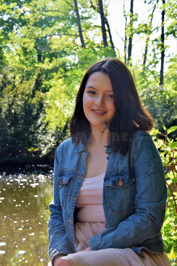 Una chica joven preciosa se coloca afuera al lado del agua fotos de archivo
