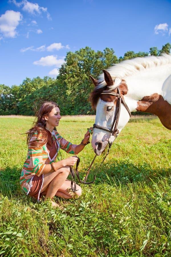 Una chica joven que camina con un caballo de la pintura imagen de archivo