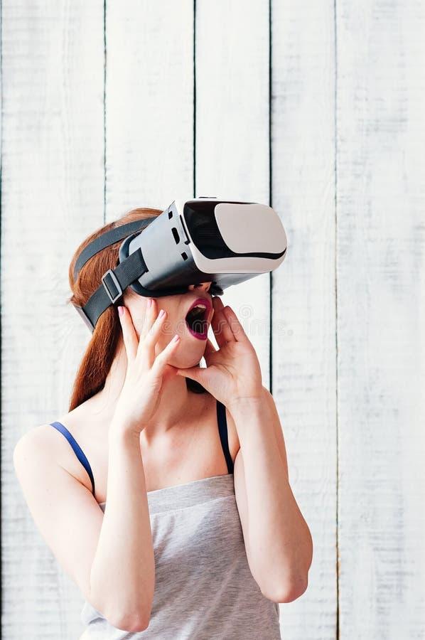 Una chica joven que lleva los vidrios de VR, excitado, llevando a cabo sus manos en f imagen de archivo