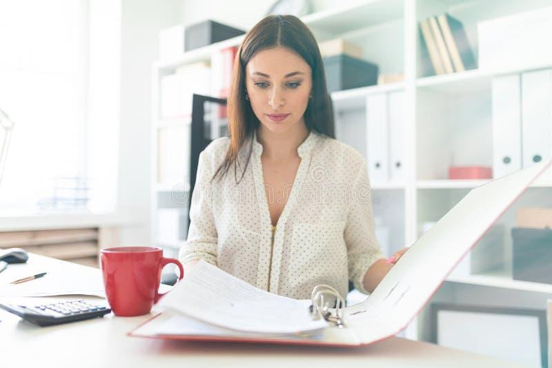 Una chica joven que se sienta en la oficina en un escritorio del ordenador y que hojea a través de una carpeta de documentos fotografía de archivo libre de regalías