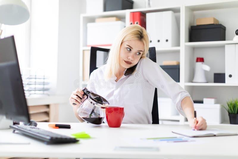 Una chica joven que se sienta en una tabla en la oficina, hablando en el teléfono y el café de colada de un pote del café fotos de archivo libres de regalías